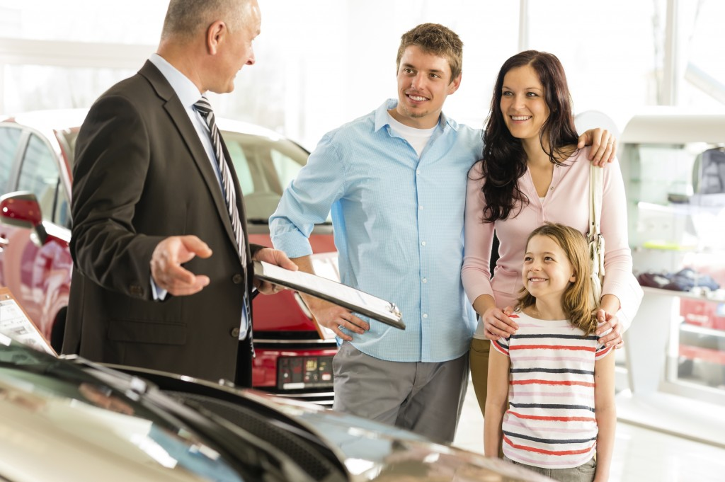 Salesman offering a car to family
