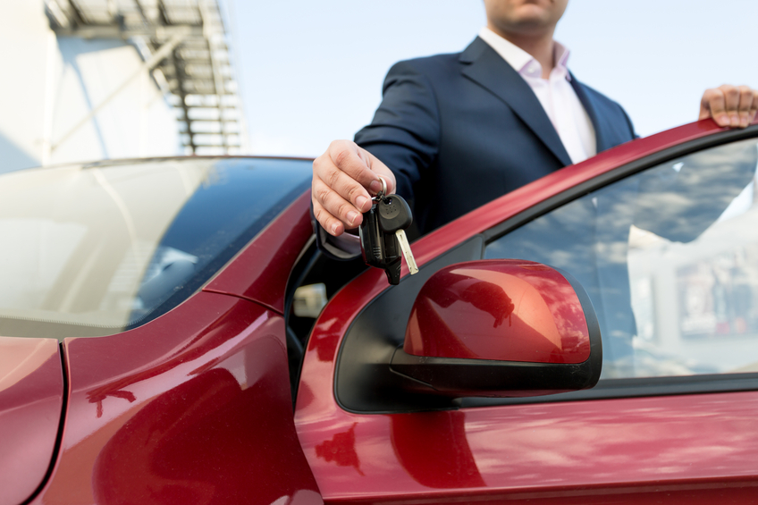 Closeup shot of handsome car salesman giving keys